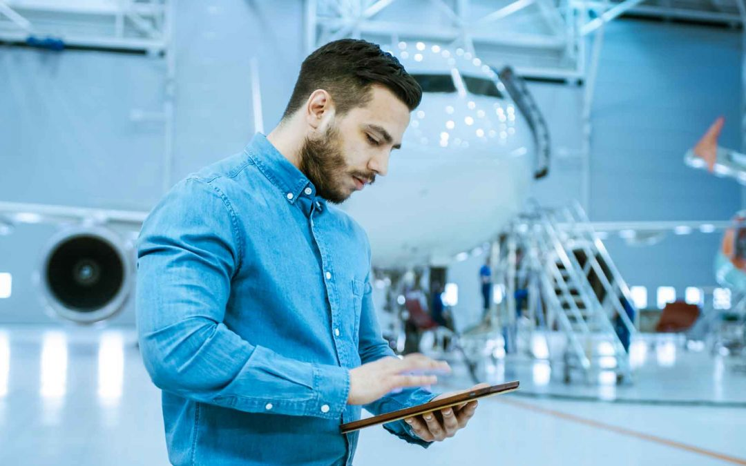 Speurviation-In-Big-Company-Hangar-Aircraft-Maintenance-Engineer-Uses-Tablet-Computer-while-Standing-Near-Big-New-Shiny-White-Plane.